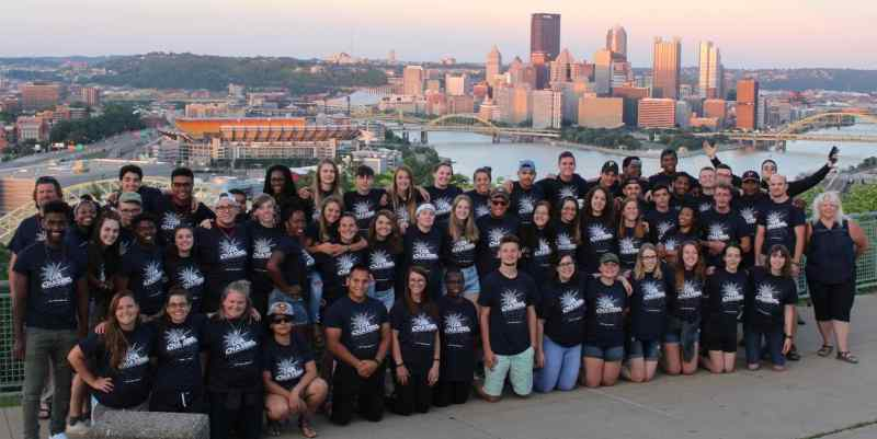 This is a large group photo of Pine Valley Camp summer staff couselors, taken on Mt. Washinton, overlooking the city of Pittsburgh, PA as the backdrop.