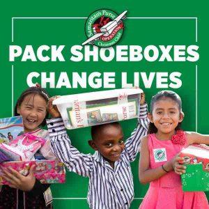 Photo of three children recieving their Operation Christmas Child shoebox.
