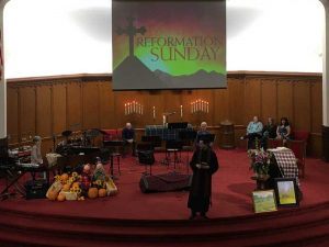 Photo of Pastor Rich at the center of the platform during Reformation Sunday activities.