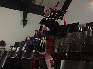 Photo of Kirby playing the bagpipes as he walks thru the balcont on his way to the front of the church.