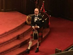 Photo of a bagpiper playing in front of the sanctuary.